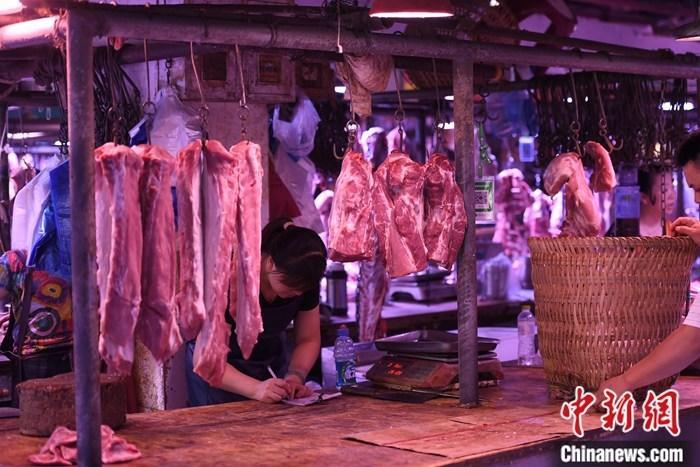 资料图:重庆一农贸市场内的商家挂满充足的猪肉。<a target='_blank' >中新社</a>记者 陈超 摄